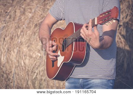 Man hands on acoustic guitar against hay roll background