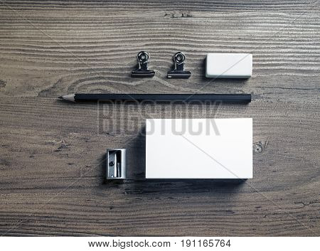 Photo of blank stationery set. Business card pencil eraser and sharpener on wood background. Mock up for ID. Top view.