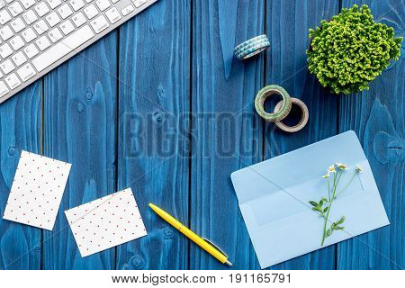 colorful work space with keyboard, sticky note and flowers for home office blue wooden desk background top view mockup