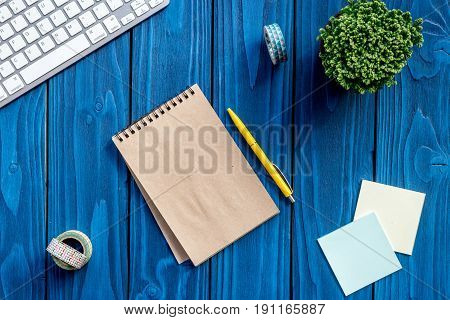 colorful home office desk with plants, notebook and keyboard on yellow background top view mock up