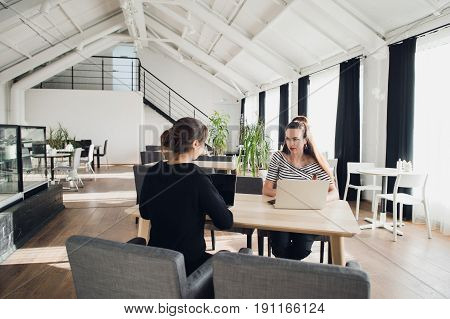 Female business team having a meeting together to discuss paperwork sitting at a table having a discussion. Two businesswomen sitting at a table with laptops and one asking another