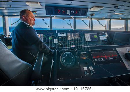 SOUTH ISLAND, NEW ZEALAND- MAY 25, 2017: Close up of a ferry boat pilot command cabin with the captain operating the machines with a beautiful view on the sea, in new zealand.