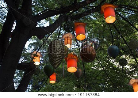 Adorned street trees. There are decorative balls balloons lamps and oil lamp