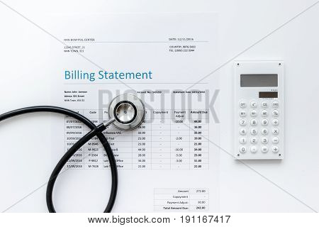 medical treatmant billing statement with stethoscope and calculator on white desk background top view