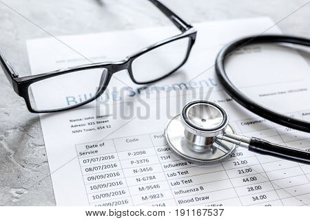health care costs with billing statement, stethoscope and glasses on stone table background