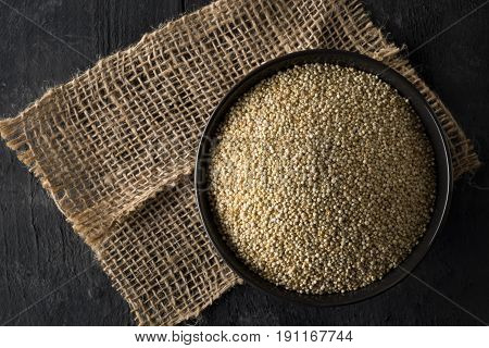 Raw whole unprocessed quinoa seed in bowl on brown rustic wood board