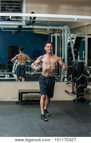 Middle age muscular man performing cable chest press exercise with back reflected in mirror and intense expression.