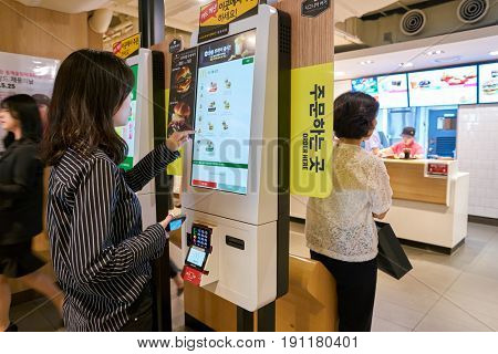SEOUL, SOUTH KOREA - CIRCA MAY, 2017: woman use McDonald's ordering kiosk. McDonald's is an American hamburger and fast food restaurant chain.