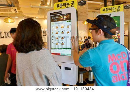 SEOUL, SOUTH KOREA - CIRCA MAY, 2017: people use McDonald's ordering kiosk. McDonald's is an American hamburger and fast food restaurant chain.