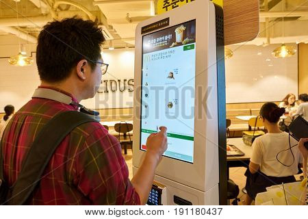 SEOUL, SOUTH KOREA - CIRCA MAY, 2017: man use McDonald's ordering kiosk. McDonald's is an American hamburger and fast food restaurant chain.