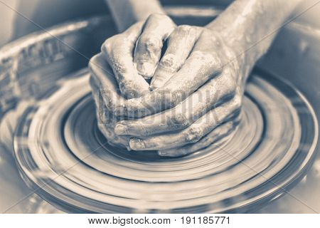 Old vintage photo. Master potter folded together hands sculpts a clay product on a potter's wheel. Hand skin stained with clay and wet