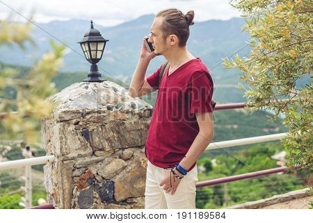 Man Traveler Talking On The Phone On A Background Of Mountains