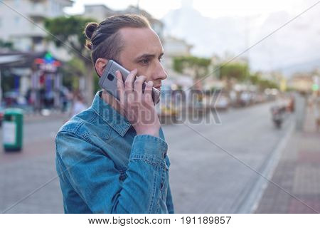 Man Traveler With Backpack Talking On The Phone In The Background Of The Street.