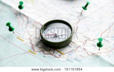 Compass and pushpin on a map