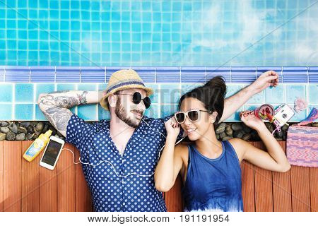 Aerial view of cheerful couple lying by the poolside enjoying summer time