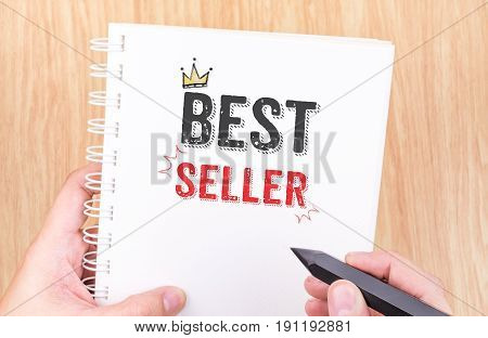 Best Seller Word On White Ring Binder Notebook With Hand Holding Pencil On Wood Table,business Conce