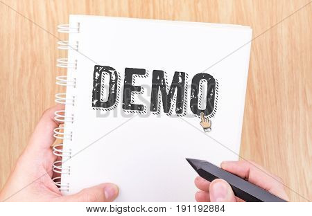Demo Word On White Ring Binder Notebook With Hand Holding Pencil On Wood Table,business Concept