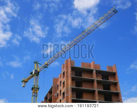 Residential brick building construction with crane on the background of blue sky