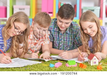 Group of children lying on floor with green carpet and drawing with pencils