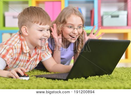 two teenagers lying on floor withn  green carpet in front of modern laptop