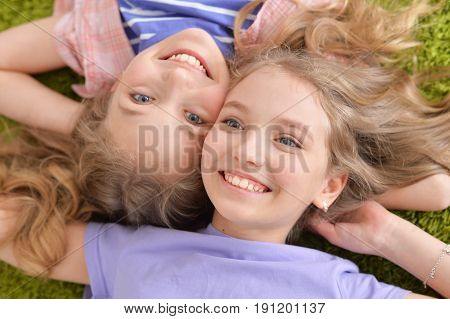 Two pretty little girls lying on green carpet and looking at camera