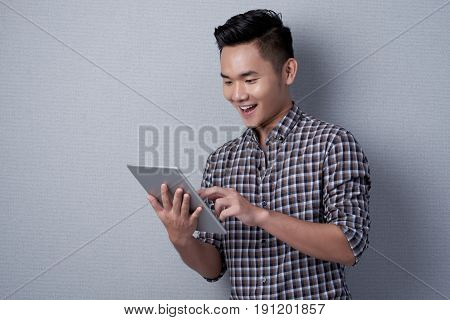 Cheerful Vietnamese man with rolled-up sleeves standing against gray wall and surfing net on modern digital tablet, waist-up portrait