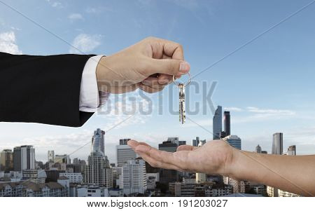 Hand giving and receiving keys with city background, buying home, real estate and house rental concepts