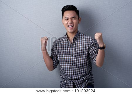 Handsome Vietnamese businessman wearing checked shirt looking at camera while triumphing with raised hands, waist-up portrait