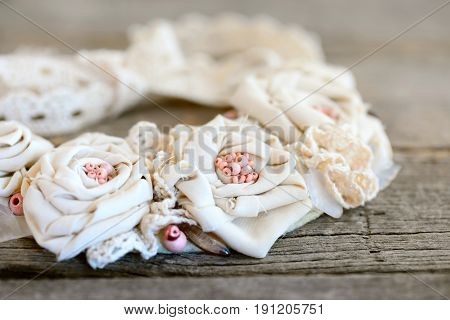 Romantic shabby chic necklace on a vintage wooden background. Beautiful flower necklace made of cotton fabric, lace ribbons and beads. Easy way to turn old fabric into jewelry. Closeup
