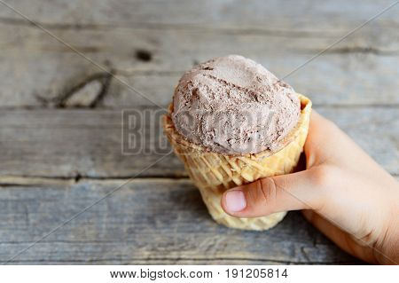 Small child holds ice cream in his hand. Child eats ice cream. Sweet chocolate ice cream in a waffle cup. Old wooden background