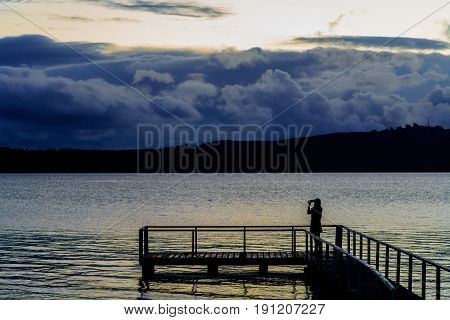 Silhouette young woman using mobile phone taking picture of beautiful Lake Taupo in the evening North Island of New Zealand