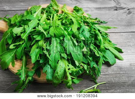 Fresh arugula leaves on wooden board rucola. Arugula rucola on gray old background.