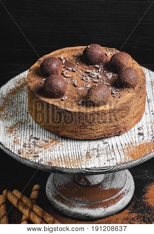 Chocolate cake torte covered with cocoa powder and decorated with truffle. Ingredients for Chocolate cake torte Chocolate waffles sticks truffles and Chocolate bars tea. Dark black wooden background.