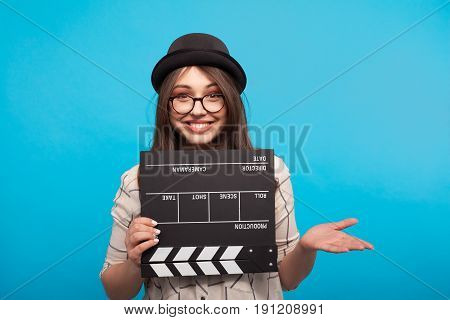 Trendy girl in hat and glasses holding clapboard and looking at camera on blue background.