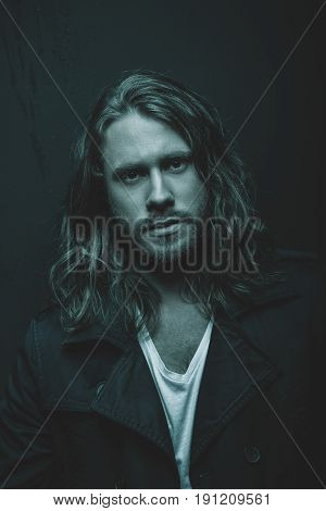 Portrait Of Handsome Stylish Bearded Young Man With Long Hair Looking At Camera