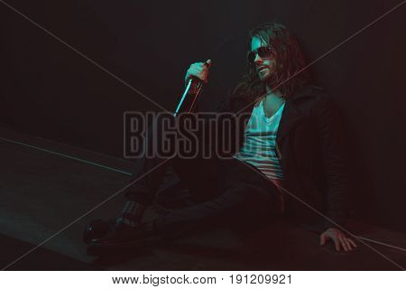 Boozer In Sunglasses Holding Bottle With Alcohol While Sitting On The Floor