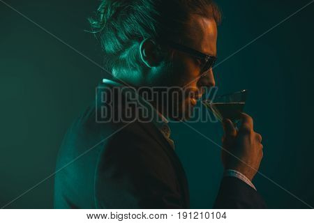 Profile Of Young Caucasian Man In Suit Drinking Cocktail From Glass