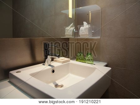 Modern restroom with steel water faucet and square white sink beneath illuminated mirror.