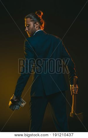 Rear View Of Young Man In Tuxedo With Ax And Us Dollar Banknotes