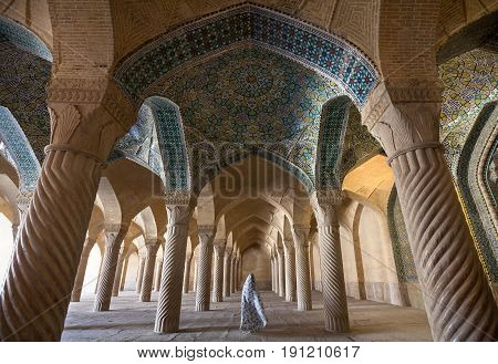 SHIRAZ, IRAN - SEPTEMBER 16, 2014: Woman in veil passing through Shabestan of Vakil Mosque. This religious place was built between 1751 and 1773, during reign of the Zand dynasty all over Iran.