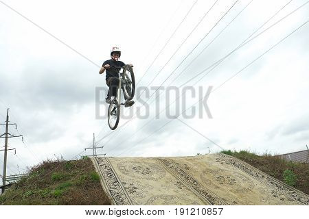 Young man jumping and riding on a BMX bicycle downhill.