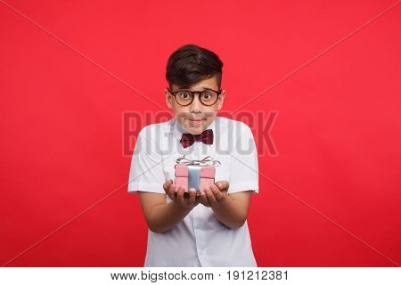 Little modest boy in glasses holding small giftbox on hands and looking at camera on red.
