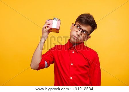 Kid in shirt and glasses holding small giftbox trying to guess present on yellow background.