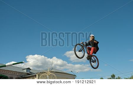 Young man jumping and riding on a BMX bicycle.