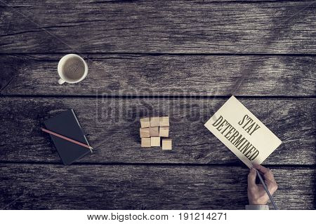 Stay Determined motivational business concept with an overhead view of the hand of a businessman writing the text on a card on a rustic wooden background with coffee wood blocks notebook and pencil.
