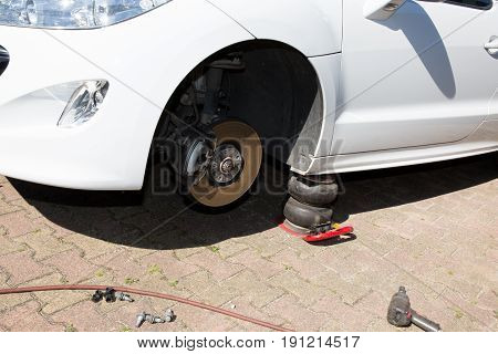 Car Without Front Wheel On Compressed Air Jack