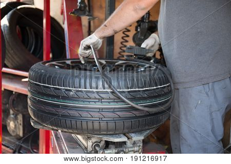 A Technician Specialist Repairs A Car Wheel And Changes The Tire With His Machine