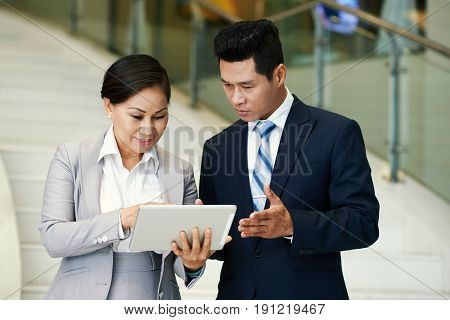 Waist-up portrait of confident middle-aged business people discussing details of joint project while going down stairs in modern office building, pretty Asian woman holding digital tablet