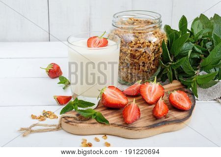 Yogurt fresh ripe strawberry granola - dietary dish on a white wooden table. Proper nutrition. Healthy breakfast.
