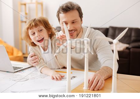 Love my daddy. Handsome delighted man holding toy turbine in left hand and looking sideways while playing with son